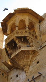 Ancient turits jut out from the walls of the fortress. Intricate stone work looks like lace against the imposing walls.