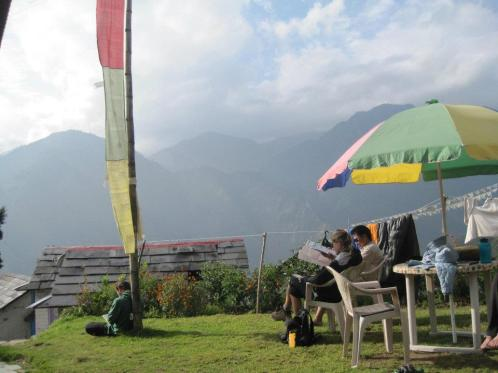 Reading in the shade of prayer flags.